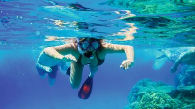 snorkeler in shallow waters of three rocks Sosua